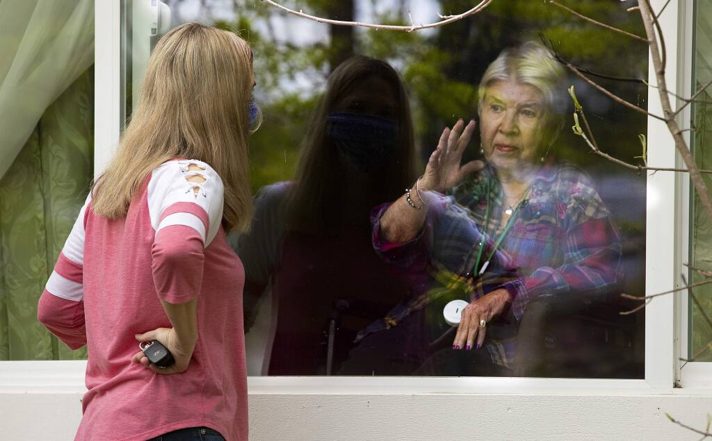 Colette Owens speaks to her mother, June Biava, through the window of Family House, a memory care home in Rohnert Park, in May 2020. Owens has staff open a side window so they can talk about doing their nails and the inability to get haircuts during the pandemic. (John Burgess / The Press Democrat)