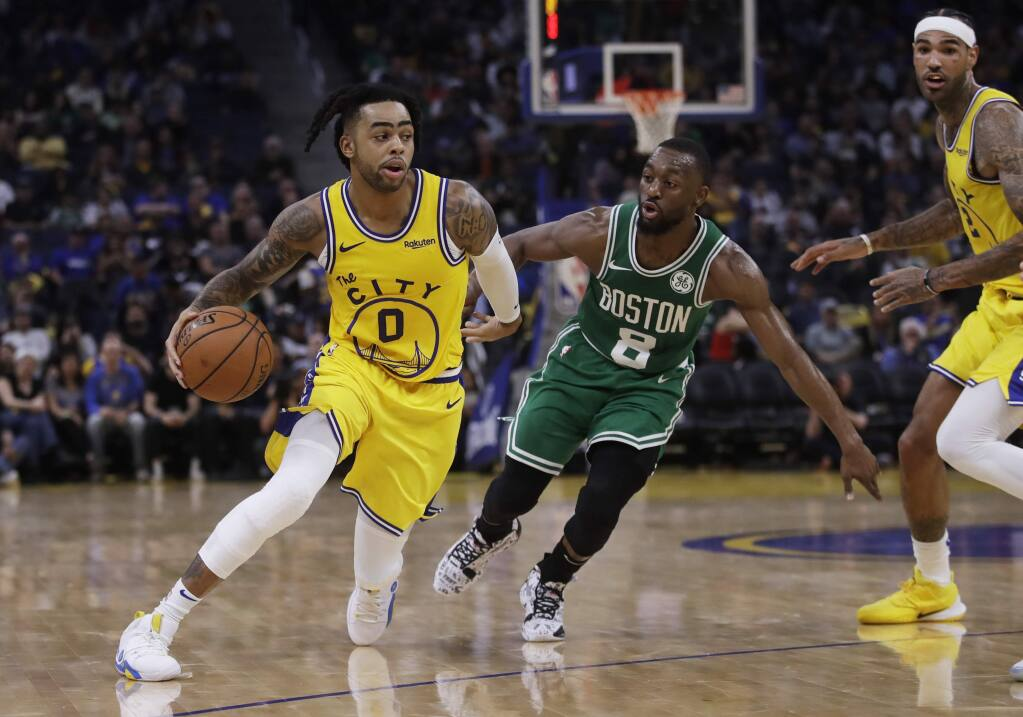 The Golden State Warriors' D'Angelo Russell, left, drives the ball past the Boston Celtics' Kemba Walker during the second half Friday, Nov. 15, 2019, in San Francisco. (AP Photo/Ben Margot)