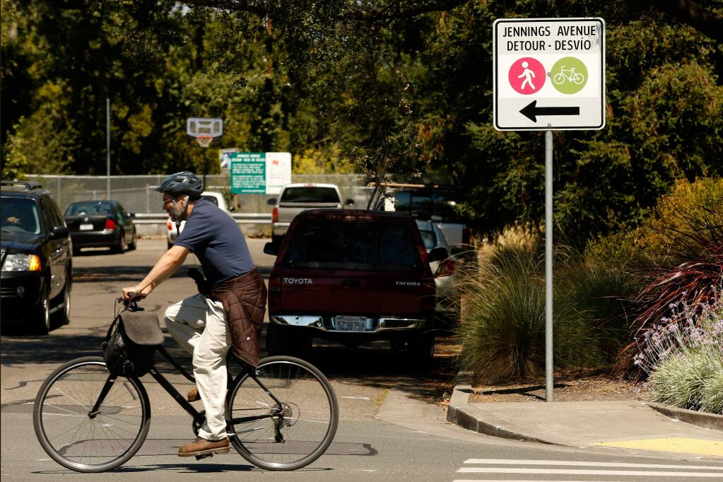 A bicyclist pedals along North Dutton Avenue past a detour sign directing pedestrian and bicycle traffic past Jennings Avenue, where a planned SMART rail crossing hasn't been built. (ALVIN JORNADA / The Press Democrat)