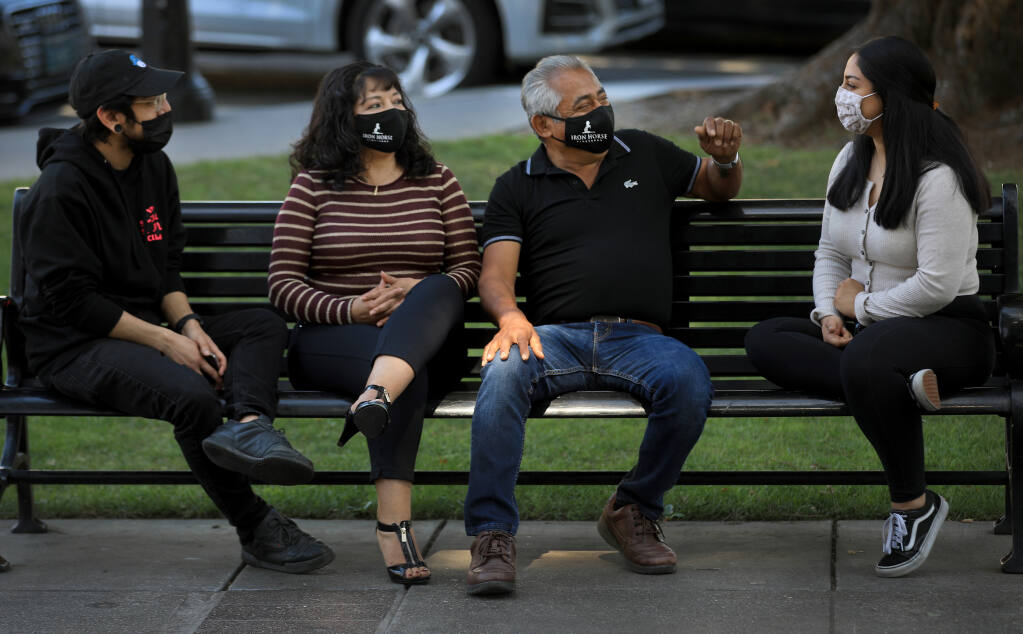 From left, Victor, Maria, Victor Sr., and Michelle Arreola all had COVID last summer and are taking no chances even after being fully vaccinated.  Just recently they've been getting out around Healdsburg and relaxing at the plaza, Friday, March 26, 2021. (Kent Porter / The Press Democrat) 2021