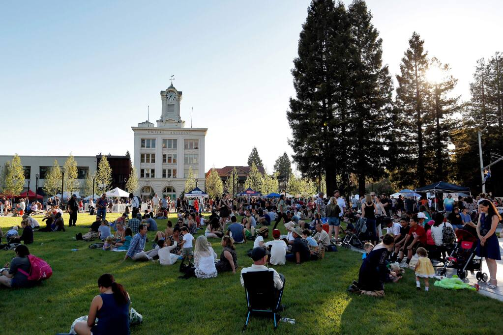 Marketgoers take respite in the shade in the newly reunified Old Courthouse Square during the first Wednesday Night Market of the season, in Santa Rosa, California, on Wednesday, May 3, 2017. (Alvin Jornada / The Press Democrat)