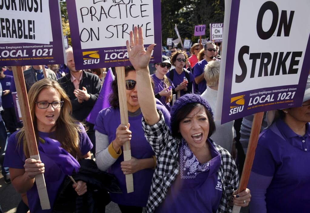 (From right) Alicia Tuso, Juana Marquez, and Teresa Baldassari attend a rally with members of the Service Employees Union Local 1021 outside the Sonoma County Administration Building in Santa Rosa, on Tuesday, November 17, 2015. (BETH SCHLANKER/ The Press Democrat)