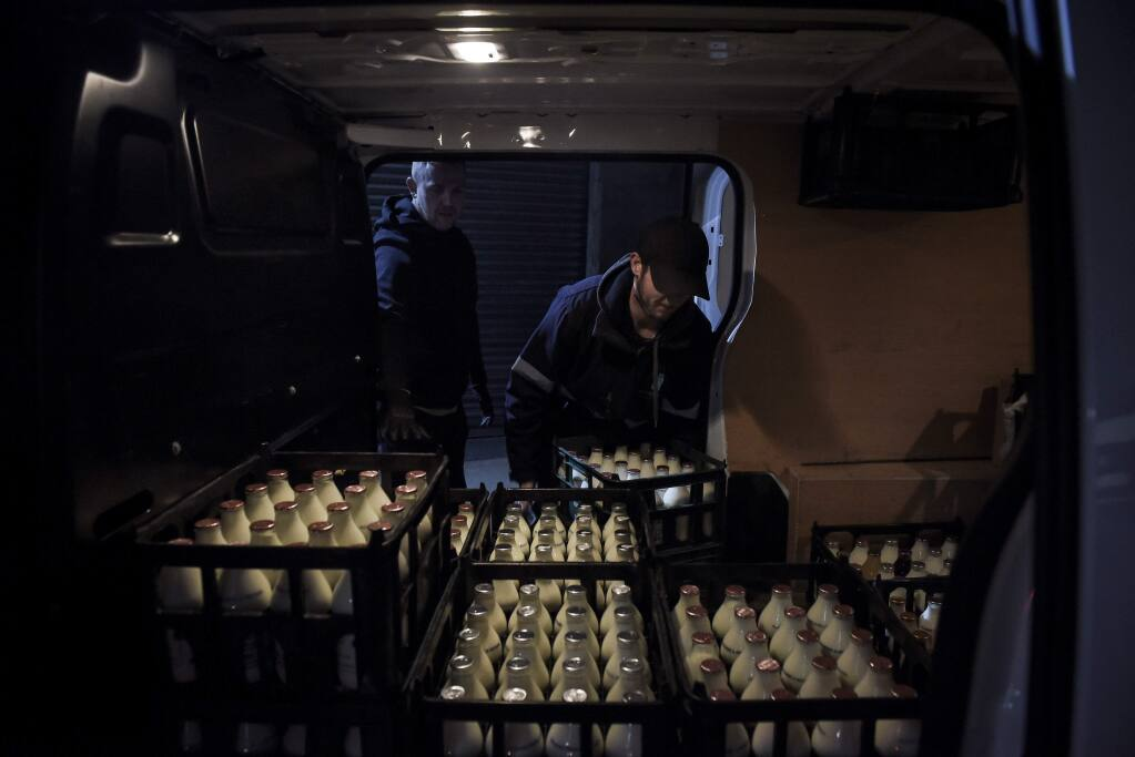 A driver loads a Modern Milkman van in Stockport, in northwest England, March 25, 2020. The milk-delivery industry, which symbolized the distant past, has taken off as people self-isolate and order their shopping from home in the aftermath of the coronavirus pandemic. (Mary Turner/The New York Times)