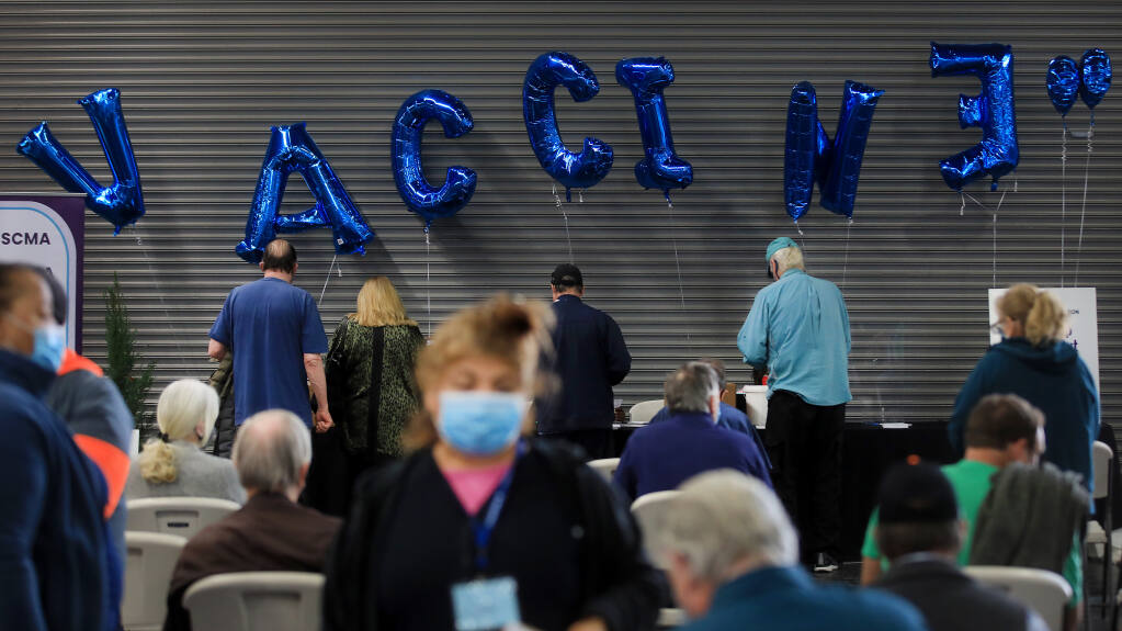 Balloons spelling 'vaccine' decorate the waiting area after  people are vaccinated against COVID-19 at the Sonoma County Medical Association's vaccine clinic at the Sonoma County Fairgrounds, Wednesday, March 3, 2021 in Santa Rosa.  (Kent Porter / The Press Democrat)