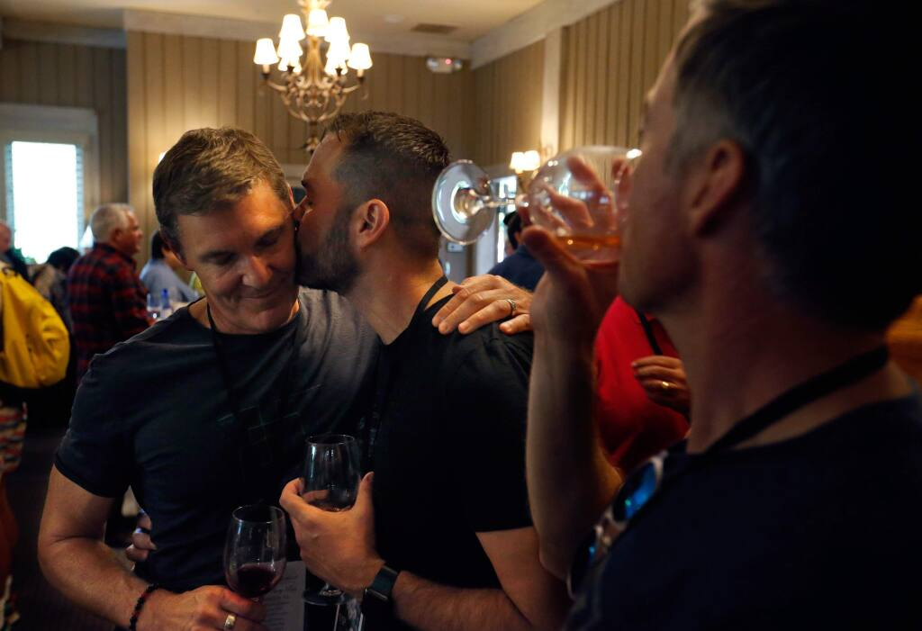 Orlando resident Steve Yacovelli, center, kisses his husband Richard Egan as they talk with friends about the Pulse night club shooting, at a reception during Gay Wine Weekend in Sonoma, California on Friday, June 17, 2016. (Alvin Jornada / The Press Democrat)
