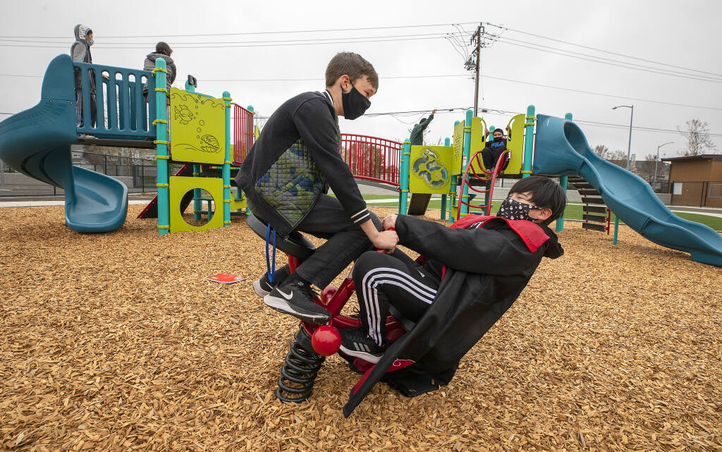 Students have fun on the new playground equipment during recess at the Spanish-English dual language immersion program Cesar Chavez Language Academy on Tuesday, April 6, 2021.  (Photo by John Burgess/The Press Democrat)