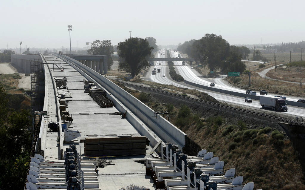 FILE - In this Oct. 9, 2019, file photo, is the high-speed rail viaduct paralleling Highway 99 near Fresno, Calif. The federal government has reached an agreement to restore nearly $1 billion in funding for California's troubled bullet train. Gov. Gavin Newsom announced Thursday night, June 10, 2021, that the U.S. Department of Transportation finalized settlement negotiations to restore money for the high-speed rail project that the Trump administration revoked in 2019. (AP Photo/Rich Pedroncelli, File)