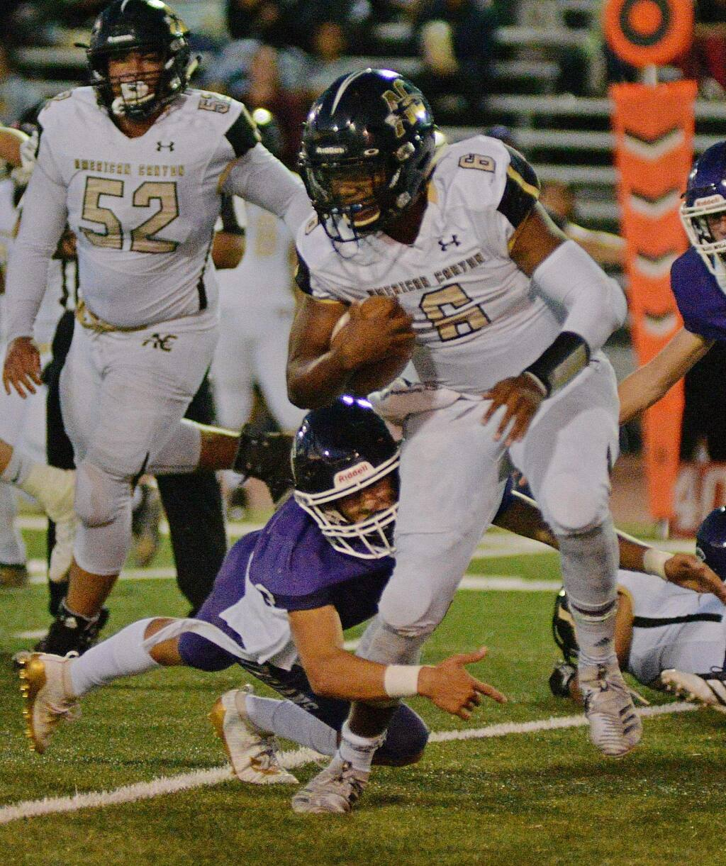 Petaluma's Jack Hartman makes an ankle tackle on American Canyon's 210-pound quarterback Vance Eshenburg in the the VVAL opening game won by American Canyon, 34-0. (Argus-Courier)
