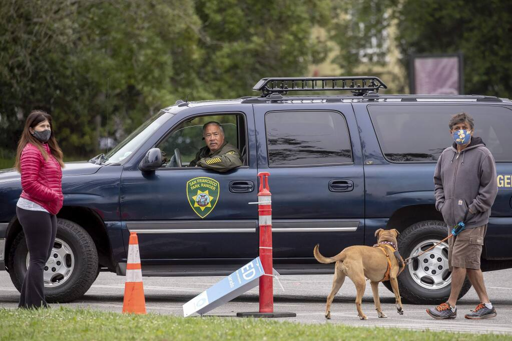 Park police and neighboring residents survey the damage in Golden Gate Park, Saturday, June 20, 2020, after statues of Junipero Serra, U.S. Grant and Francis Scott Key were toppled and graffiti was spray painted over many walls and pedestals. (Karl Mondon/Bay Area News Group via AP)