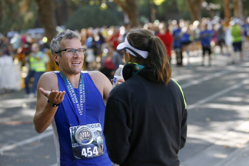 Abraham Sheppard tries to argue his case with Beth Carter, the pace team coordinator for the Santa Rosa Marathon, after he failed to qualify for the Boston Marathon because of an .9-mile detour accidentally taken by the pace-setter. Photo taken at the finish of the Santa Rosa Marathon at Juilliard Park on Sunday, August 28, 2016 in Santa Rosa, California . (BETH SCHLANKER/ The Press Democrat)