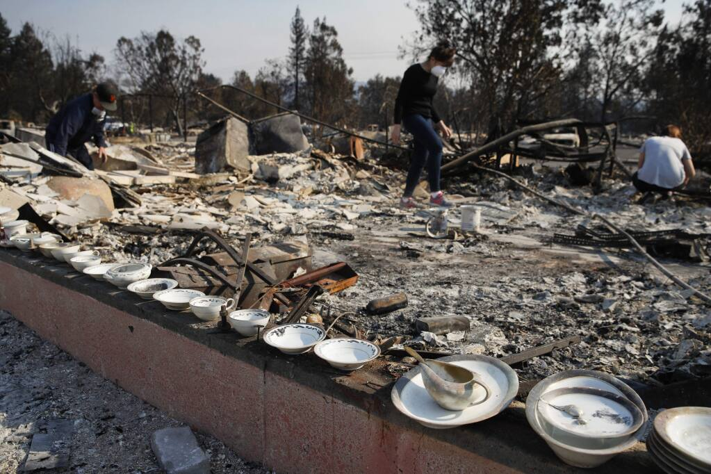 A set of salvaged china that Karen Curzon, background center, inherited from her grandmother lie on the foundation of her home that was destroyed by a wildfire in the Coffey Park neighborhood. On Oct. 15, 2017 she said, 'We are going to rebound, rebuild and get this community back.' (AP Photo/Jae C. Hong)