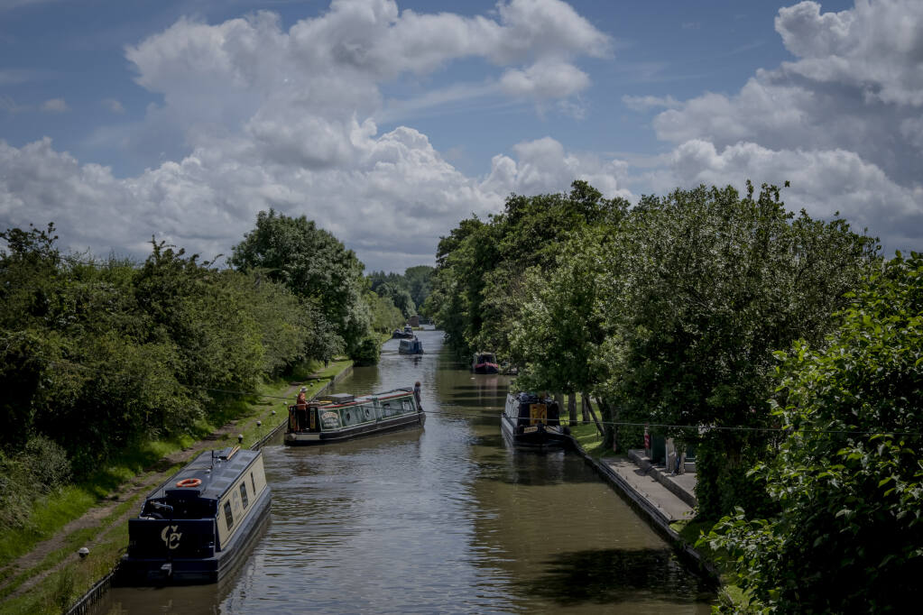 Canal boats on the Grand Union Canal near Daventry, England, on July 4, 2021. More people are calling England's canals — and the narrow boats used to navigate them — home as remote work options in the pandemic's wake make a mobile lifestyle more possible. (Andrew Testa/The New York Times)