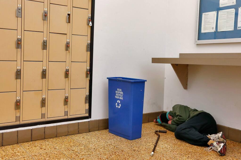 A homeless man sleeps on the floor inside the post office lobby in downtown Santa Rosa, California on Thursday, January 5, 2017. (Alvin Jornada / The Press Democrat)