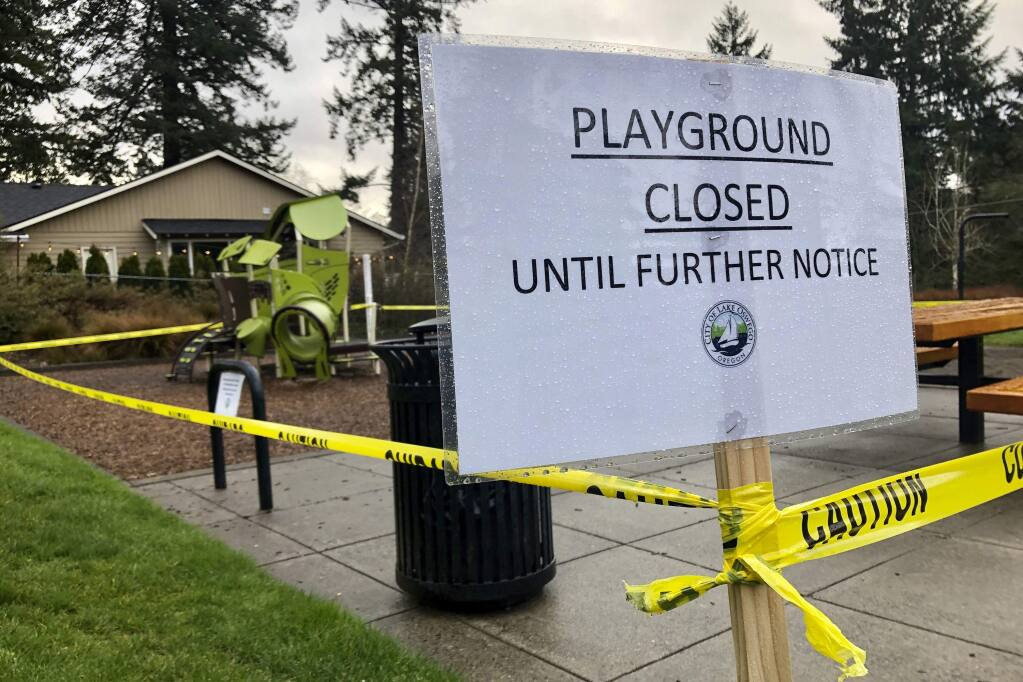 Police caution tape surrounds a playground in Lake Oswego, Ore., on Tuesday, March 24, 2020, the day after Gov. Kate Brown issued a statewide stay-at-home order that closed many businesses, as well as all playgrounds, basketball courts and sport courts. As families across the country and the globe hunker down at home, it's another danger, equally insidious if less immediately obvious, that has advocates deeply concerned: A potential spike in domestic violence, as victims spend day after day trapped at home with their abusers. (AP Photo/Gillian Flaccus)