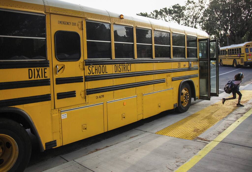 FILE - In this Oct. 18, 2018 file photo, a student hops off the school bus at Dixie Elementary School in San Rafael, Calif. The Dixie School District board in the California city of San Rafael plans to vote on whether to keep its name, which critics say it is linked to the Confederacy and slavery and supporters maintain is it named after a Native American woman. (Gabrielle Lurie/San Francisco Chronicle via AP, File)