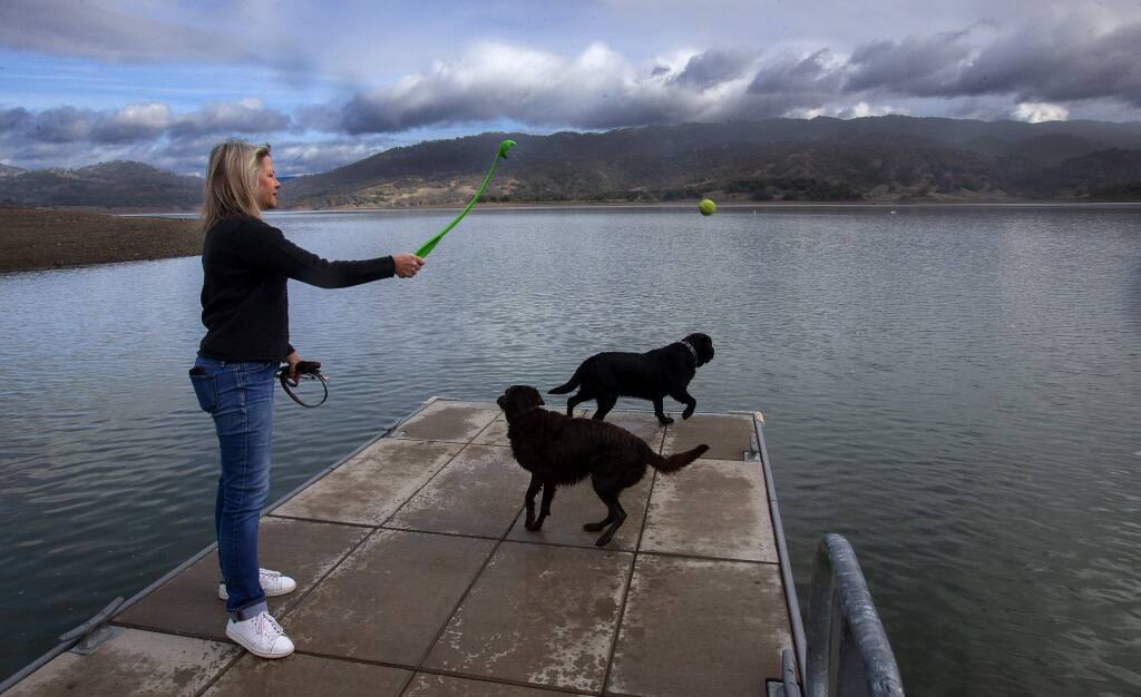 Kristin Groessl of Ukiah throws a ball for her dog at Lake Mendocino where water managers will impound up to 3.8 billion extra gallons of water this winter in the first-ever test of a program that relies on advanced weather forecasting. (JOHN BURGESS/ PD)