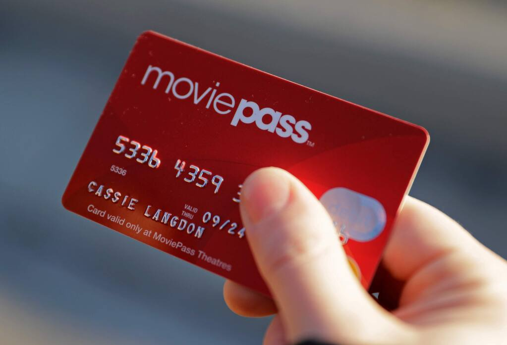 FILE - In this Jan. 30, 2018, file photo, Cassie Langdon holds her MoviePass card outside AMC Indianapolis 17 theatre in Indianapolis. MoviePass, Inc. was an American subscription-based ticket service headquartered in New York City. Founded in 2011, the service initially allowed subscribers to purchase up to three movie tickets per month for a discounted monthly fee. AP Photo/Darron Cummings, File)
