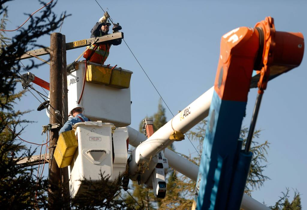 A PG&E crew repairs power lines destroyed by the Tubbs fire along Wikiup Drive in Santa Rosa, California on Wednesday, Oct. 18, 2017. (ALVIN JORNADA/ PD)