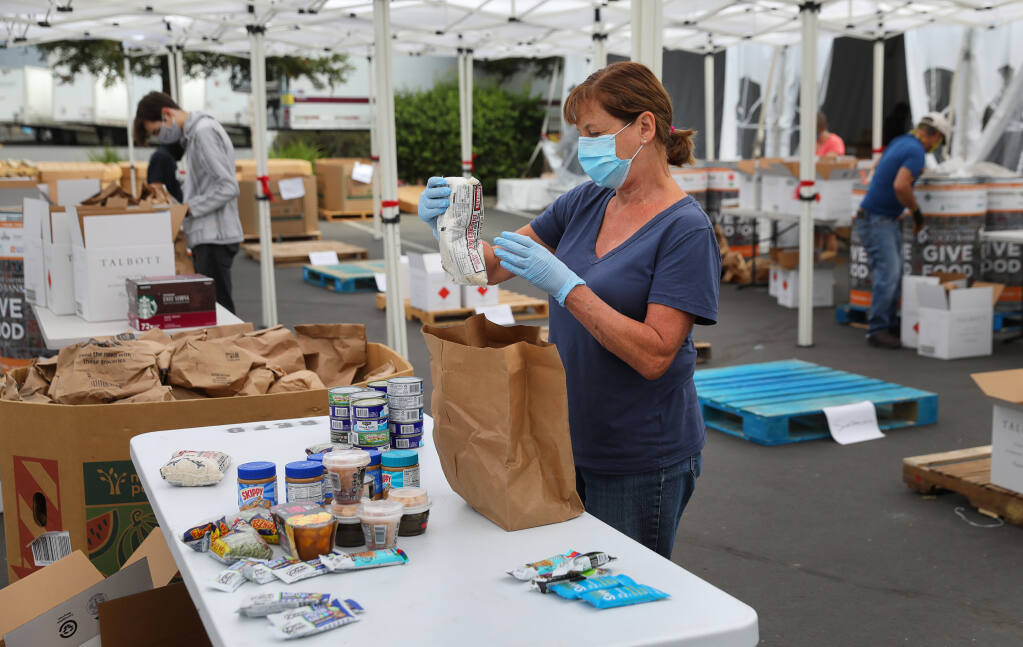 Volunteer Jeanne DeLario sorts food donated to the Redwood Empire Food Bank in Santa Rosa on Friday, July 17, 2020.  (Christopher Chung / The Press Democrat)