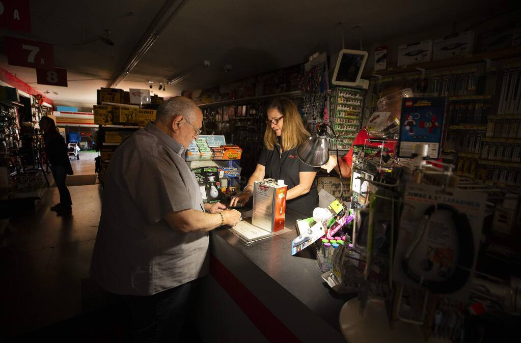 Tom Hyde picks up a can of fuel for his Coleman camp stove from Kim Scheffer at the Village True Value Hardware store in Santa Rosa on Wednesday, Oct. 9, 2019. The store used a generator to run a light, the register and a dial-up credit card machine to serve customers during the power outage. (JOHN BURGESS/ PD)