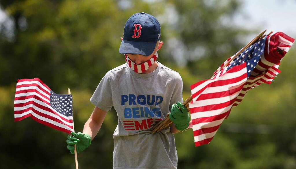 Willy Moessing, 8, looks for the graves of veterans to place flags on for Memorial Day at Santa Rosa Memorial Park, in Santa Rosa on Friday, May 22, 2020. (Christopher Chung/ The Press Democrat)