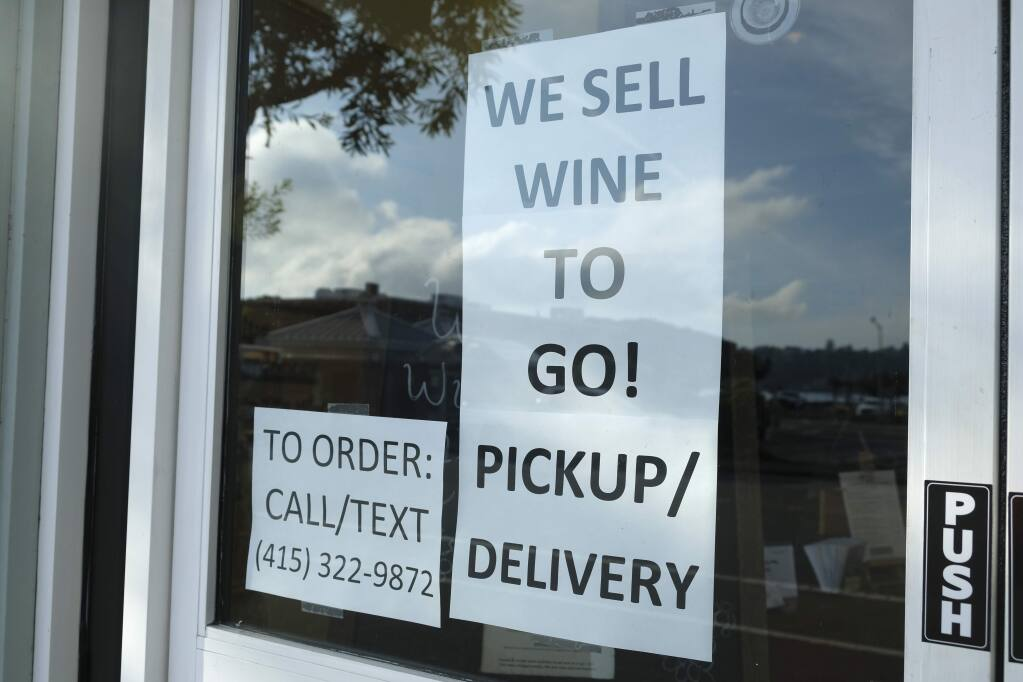 A sign in the window of The Bacchus & Venus advertises they are selling wine to go  March 17, 2020, in Sausalito. The allowance of restaurants to sell beverage alcohol to go was among dozens of accommodations the California Bureau of Alcoholic Beverage Control made for businesses significantly impacted by coronavirus pandemic public health limitations on commercial activity. A lingering legal question is how many of these allowances will become permanent. (AP Photo/Eric Risberg)