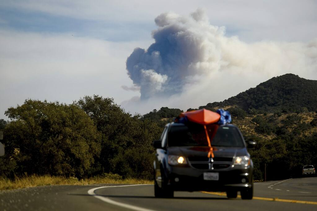 Seen from Santa Ynez, Calif., smoke from the Cave fire plumes over Los Padres National Forest on Tuesday, Nov. 26, 2019. (AP Photo/Noah Berger)