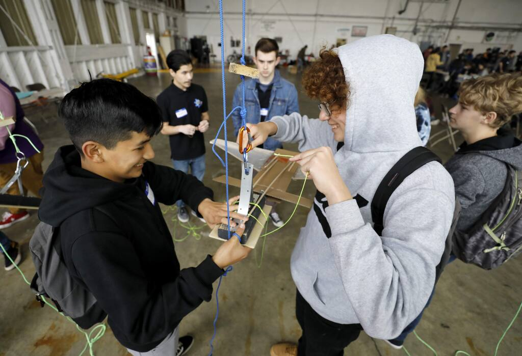 Windsor High School students Alex Pacheco, 14, left, and Carlos Lara, 14, work on creating a glider to safely deliver an egg from 20 feet up in the air during an event hosted by Windsor High's Axis STEM Academy. Photo taken at the Sonoma Jet Center in Napa on Thursday, January 31, 2019. (BETH SCHLANKER/ The Press Democrat)