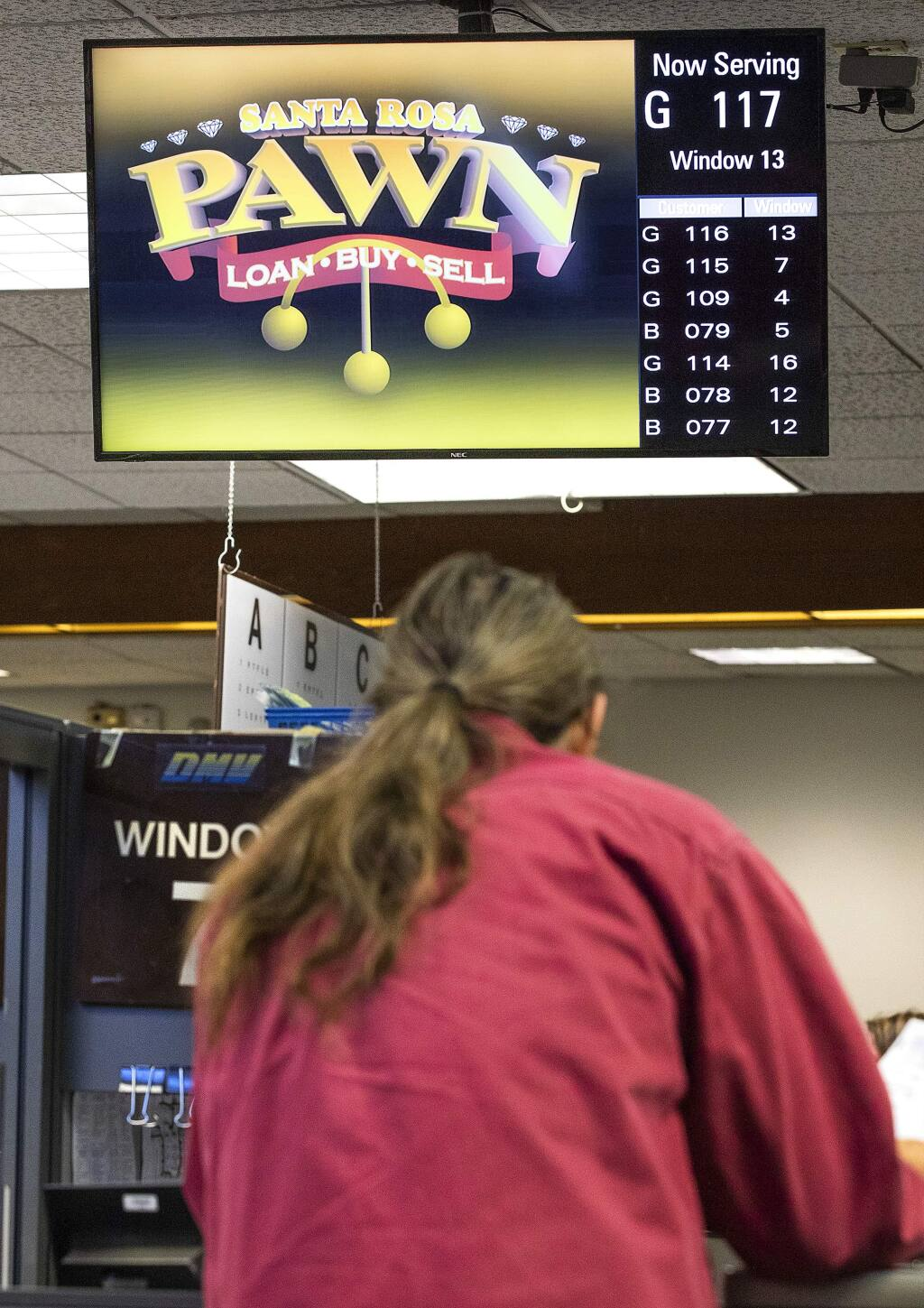 The Motor Vehicle Network, a non-governmental business, brings in hundreds of thousands of dollars for advertising next to customer numbers on television screens at DMV offices across the state including the Santa Rosa office. (photo by John Burgess/The Press Democrat)