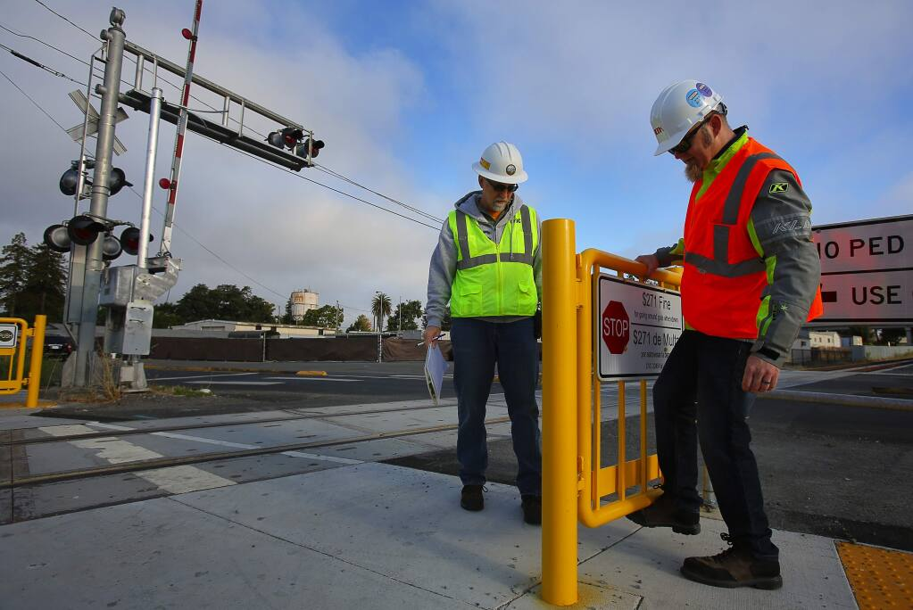 California Public Utilities Commission Safety and Enforcement Division utitilites engineer Dave Stewart, left, and Aaron Parkes, systems consultant with LTK Engineering Services look over a pedestrian exit gate at the rail crossing, at Sebastopol Road, in Santa Rosa, on Friday, August 12, 2016. (Christopher Chung/ The Press Democrat)
