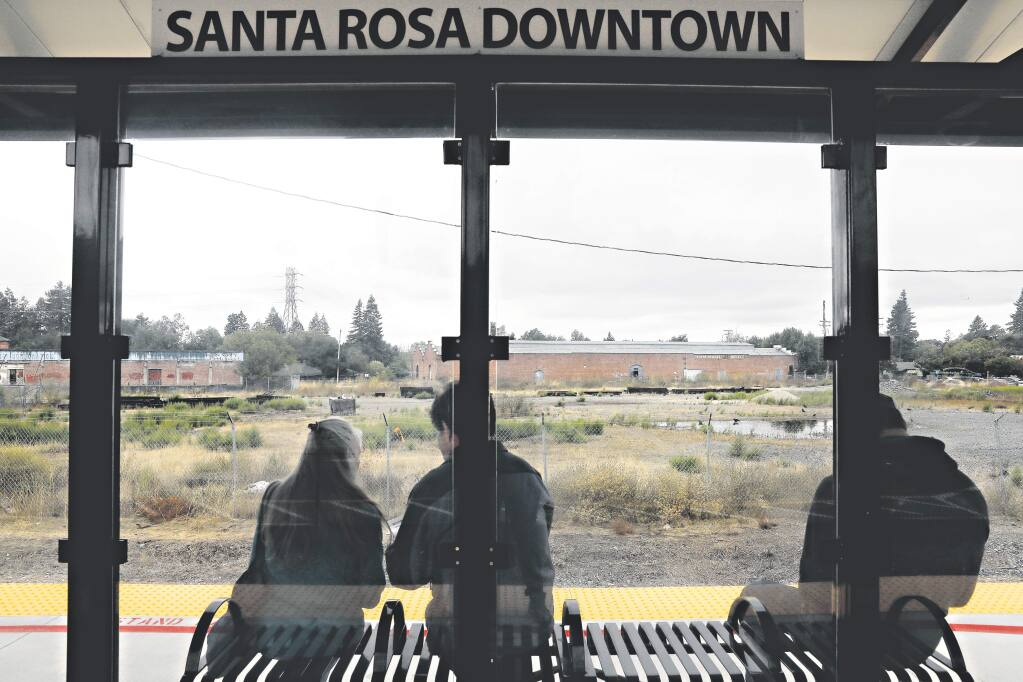 People wait at the downtown SMART station which is across the tracks from a 5-acre piece of property for sale in Santa Rosa on Thursday, October 4, 2018. (Beth Schlanker/ The Press Democrat)