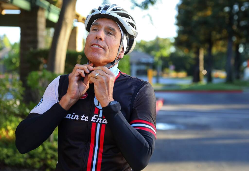 Troy Tuscher straps on his helmet before going for a bike ride in Healdsburg on Thursday, July 20, 2017. Tuscher will be competing in his third full Ironman competition.(Christopher Chung/ The Press Democrat)
