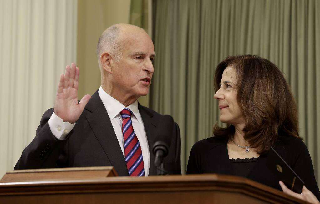 California Gov. Jerry Brown takes the oath of office as his wife, Anne Gust Brown, looks on during his inauguration at the state Capitol Monday, Jan. 5, 2015, in Sacramento, Calif. When Brown takes the oath of office Monday, it will be the first time a California governor will be sworn in to a fourth term. The 76-year-old Democrat, who held office from 1975 to 1983 before term limits and returned for a third term in 2011, delivered a joint inauguration and state of the state address in the Assembly chamber at the state Capitol. (AP Photo/Rich Pedroncelli)