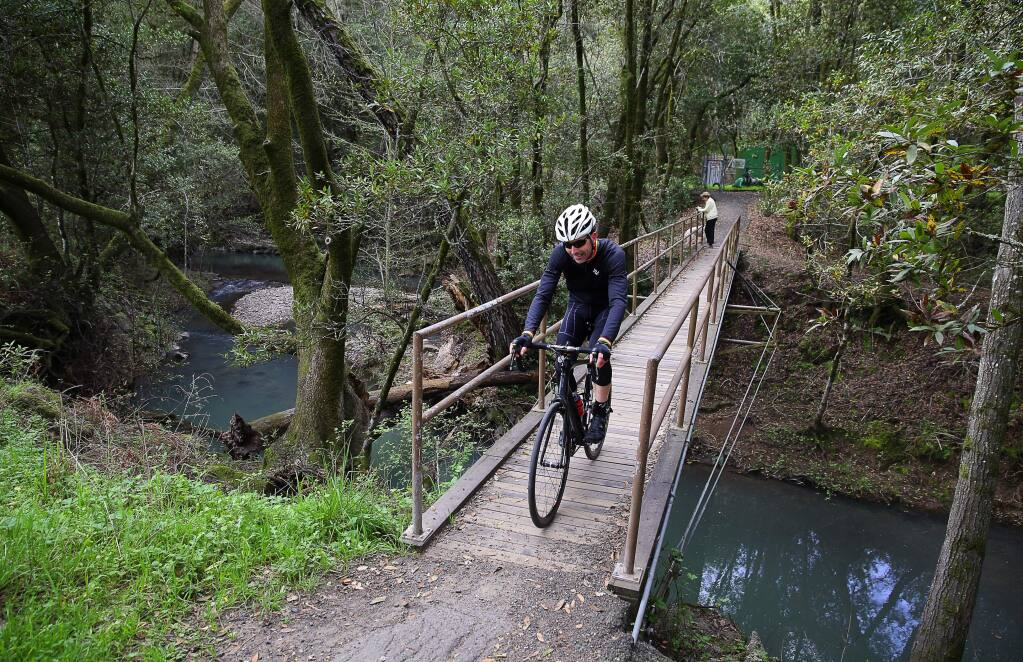 Cyclist Jay Abraham crosses a bridge from the trail off of Channel Drive towards Stone Bridge Road in the Oakmont area of Santa Rosa on Thursday, March 16, 2017. (Christopher Chung/ The Press Democrat)
