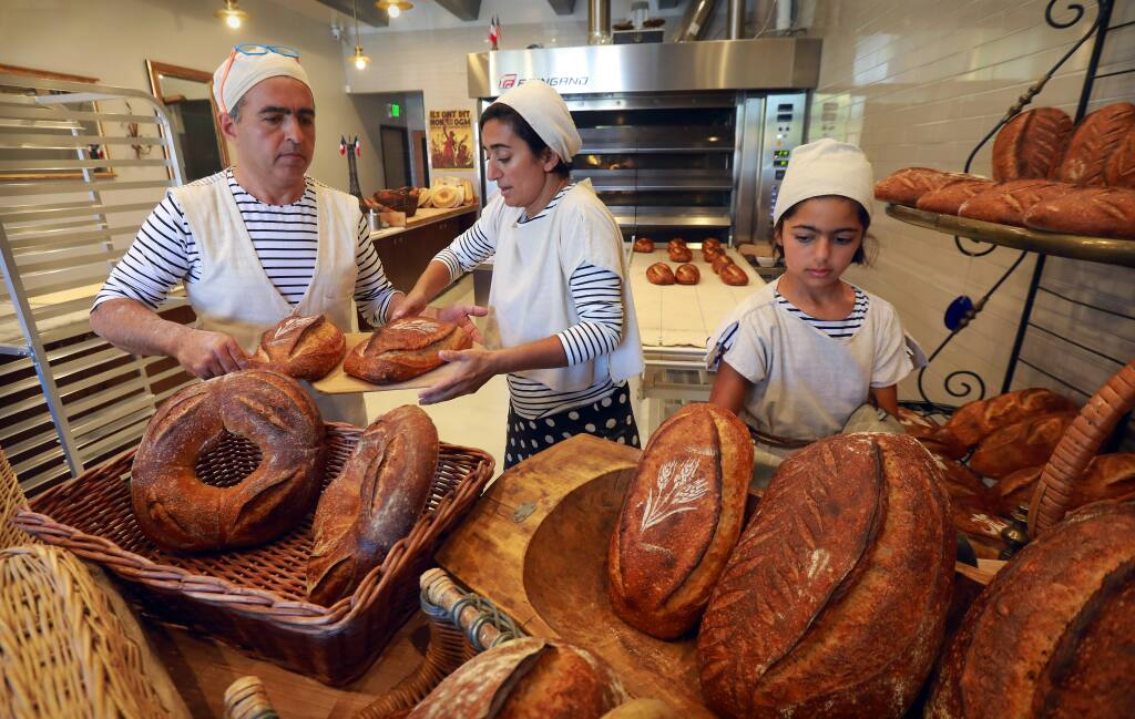 photos by John Burgess / The Press DemocratNas Salamati, left, runs Goguette Bakery on Montgomery Drive in Santa Rosa with help from his wife, nutritionist Nagine Shariat, and their 11-year-old daughter, Soraya. Below, Nas removes a 3-foot long loaf of pain de partage (bread to share), one of a variety of breads he bakes, out of the oven.