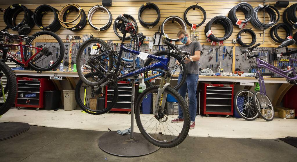 Bike Peddler store manager Chris Wells does a final check on a mountain bike before completing a sale to a customer in Santa Rosa on Monday. (Photo by John Burgess/The Press Democrat)