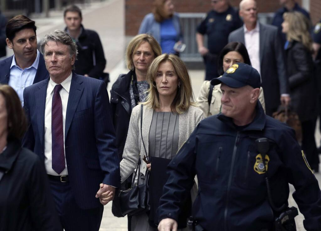 Felicity Huffman, center, departs federal court with her brother Moore Huffman Jr., left, Monday, May 13, 2019, in Boston, where she pleaded guilty to charges in a nationwide college admissions bribery scandal. (AP Photo/Steven Senne)