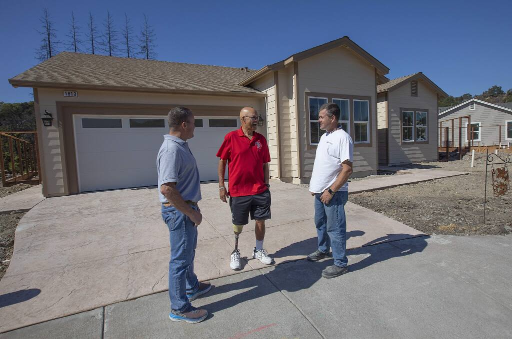 Homeowner Tom Francois, center, talks with Dave, right, and Eric Keith of Sonoma County builders in front of his rebuilt home, the first to be completed in Fountaingrove, on Sonterra Ct. (photo by John Burgess/The Press Democrat)