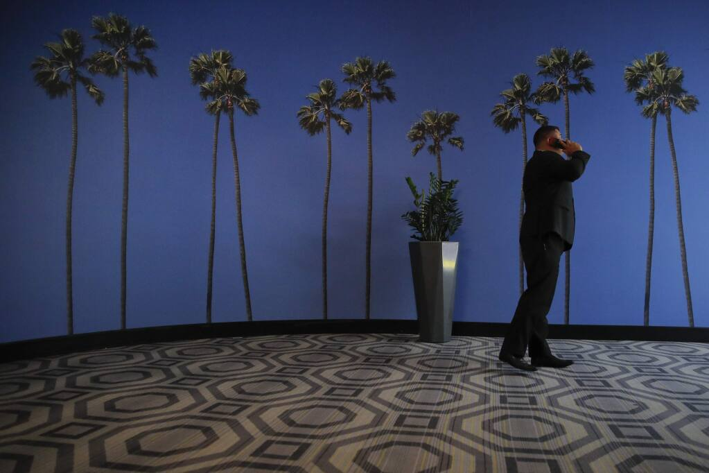 FILE - In this May 4, 2018, file photo a man talks on the phone in a hallway adorned with the palm tree-printed wallpaper at a hotel near the Los Angeles International Airport in Los Angeles. New tools are coming to help fight robocall scams, but don't expect unwanted calls to disappear. (AP Photo/Jae C. Hong, File)