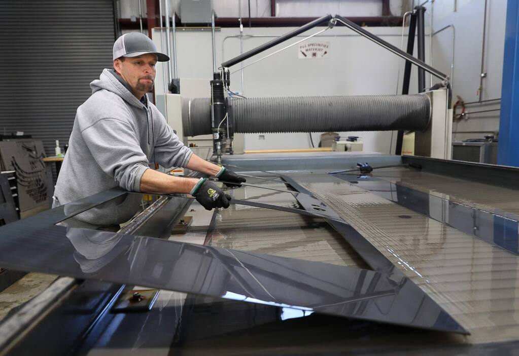 Dustin Holbrook lifts a steel frame for a custom cut door from the water jet machine at P&L Specialties, in Santa Rosa on Thursday, January 3, 2019. (Christopher Chung/ The Press Democrat)