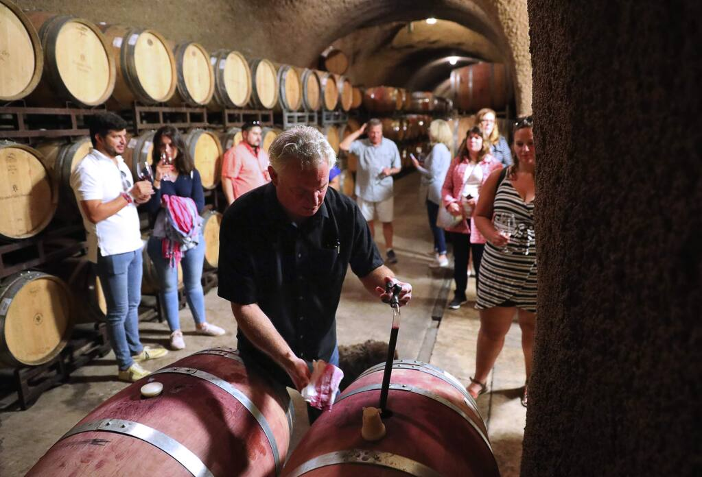 Tim Yeakel, tasting room lead, pulls a sample of wine from a barrel for a group of visitors in the Alexander Valley Vineyards cave, in Healdsburg on Tuesday, August 21, 2018. (Christopher Chung/ The Press Democrat)