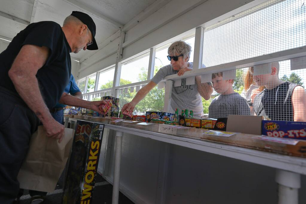 Joe Phaby, left, helps customer Sam Dakin, accompanied by his son, Jolyon Dakin, and nephew Cooper Jeffree, at the fireworks stand operated by VFW Post 3919, at the Fiesta Shopping Center in Sebastopol on Friday, June 28, 2019. (Christopher Chung / The Press Democrat)