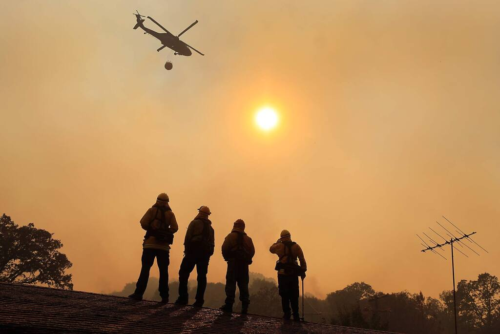 Firefighters stand watch on a roof during the River fire on Scotts Valley Road near Lakeport on Thursday, Aug. 2, 2018. (KENT PORTER/ PD)