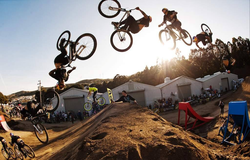 A demonstration of the athleticism and acrobatic skills that can lead to victory at a pro mountain bike competition: Andreu Lacondeguy, center, does a double backflip to clinch a victory.