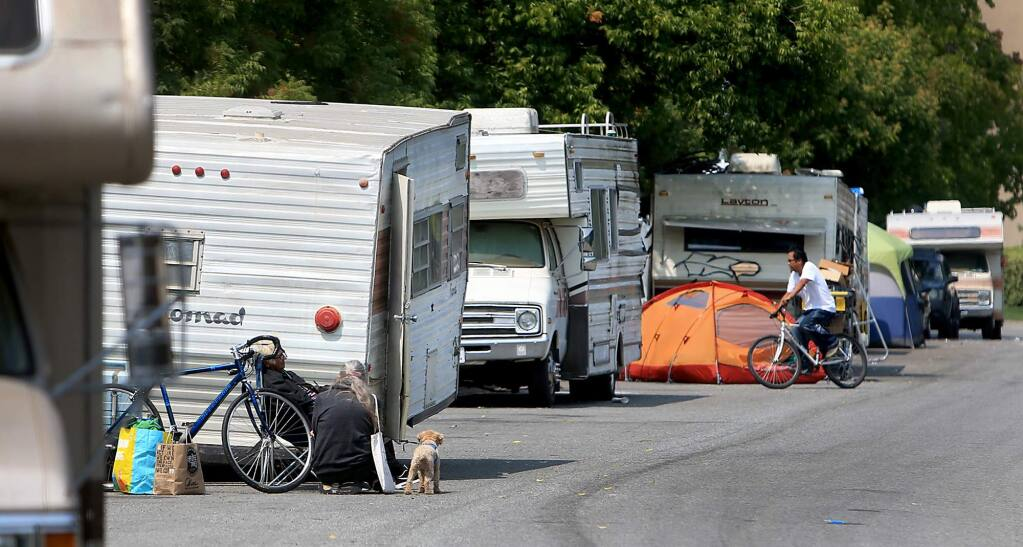 Adrienne Lauby, of Homeless Action, with dog, talks with a resident of a motor home community at the Northpoint Corporate Center in Santa Rosa, Friday, August 24, 2018 that were displaced by last years fires. Homeless Action and St. Vincent de Paul have teamed up to raise funds to help people pay their DMV registration costs for the vehicles. (Kent Porter / The Press Democrat) 2018