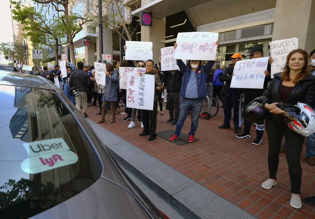 FILE - In this May 8, 2019,, file photo, Uber and Lyft drivers carry signs during a demonstration outside of Uber headquarters in San Francisco. Companies like Uber and Lyft helped create the so-called gig economy. Legislation pending in the Assembly could set a clearer standard for who, exactly, is an independent contractor with a 'gig' and who has the rights of a full-fledged employee. Backed by labor unions, the bill, AB5, could expand rights and benefits to workers now labeled independent contractors, in turn upending some industries. (AP Photo/Eric Risberg, File)