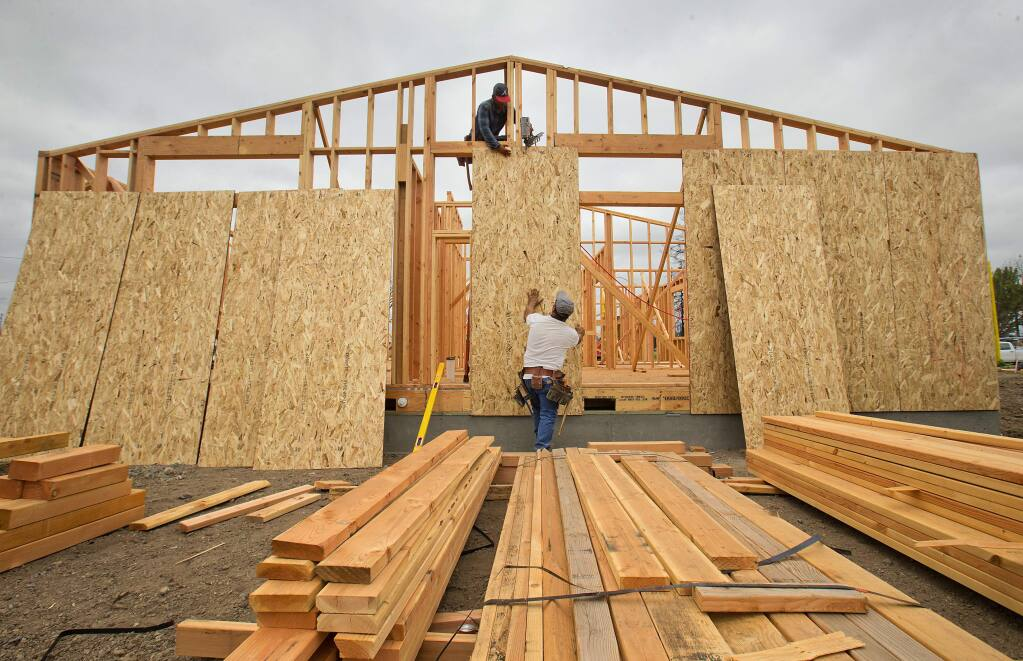Jason, top, and Jesus Garcia frame a Mocha Ln. home in Coffey Park built by Shook & Waller Construction of Windsor. (photo by John Burgess/The Press Democrat)