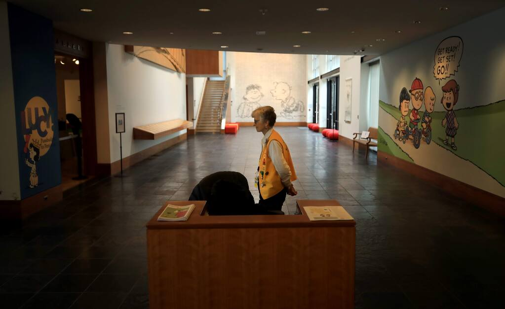 At the Charles M. Schulz Museum in Santa Rosa, volunteer docent Kay Pugh silently paces as she waits to inform visitors to the museum about the history of Peanuts characters, Friday, March 13, 2020. Attendance at the museum is down due to COVID-19.(Kent Porter / The Press Democrat) 2020