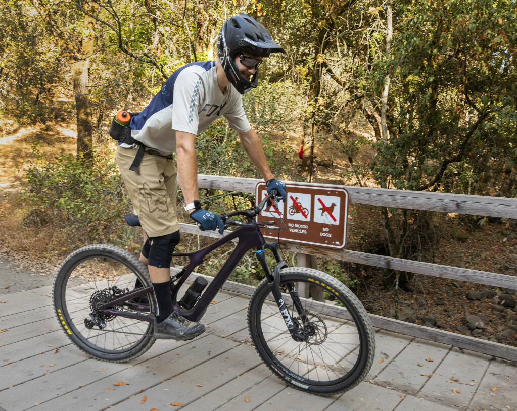 Garrett Thompson rides his Levo SL e-mountain bike past a no motor vehicles sign at Trione-Annadel State Park on Tuesday, Aug. 17, 2021. E-bikes are not allowed on trails in the park, but with a lack of park rangers to enforce the rules the number of battery powered bikers has increased with their popularity. (John Burgess/The Press Democrat)