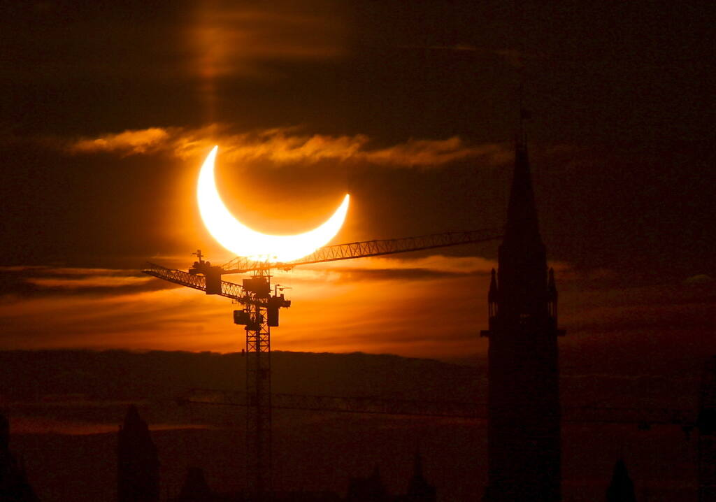 An annular solar eclipse rises over construction cranes and the Peace Tower on Parliament Hill in Ottawa on Thursday, June 10, 2021.  (Sean Kilpatrick/The Canadian Press via AP)